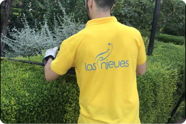 """Hombre realizando servicio de jardinería con el logo """"Las Nieves"""""""