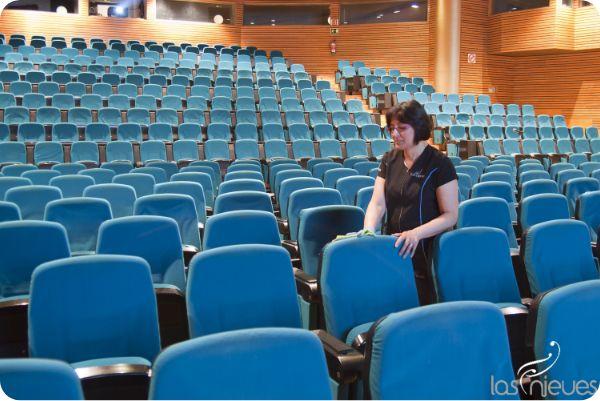 Mujer realizando el servicio de limpieza en un teatro