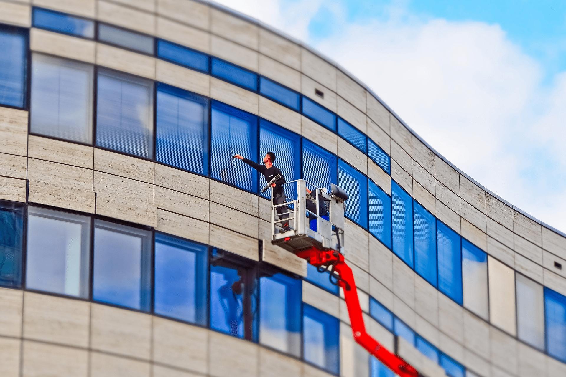 Empresa de limpieza limpiando los cristales exteriores de un edificio.